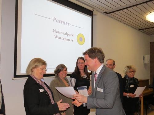 Staatssekretär Dr. Ulf Kämpfer gratuliert Helga Jessen aus Büsum zur Verlängerung ihres Nationalpark-Partner-Vertrages. (Quelle: Hecker / LKN-SH)