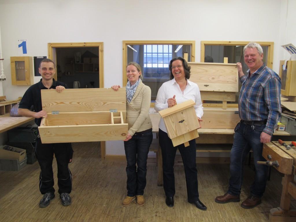 Frank Ehing, Johanna Kulessa, Petra Bernert und Michael Wiedmaier (v.l.n.r.) zeigen die Fledermaus- und Steinkauzkästen, die in der Schreinerei der JVA Rottenburg gefertigt werden.